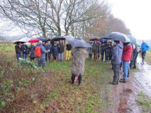 Circa dertig mensen, familie, vrienden, en oud-collega's, hebben zich verzameld rondom de te onthullen bank ter ere van Dick Brinkhuizen.